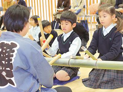 竹で作った楽器でお囃子のリズムを刻む1年生。