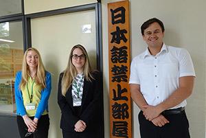教室の看板の前で、左からダニエル先生、ジェシカ先生、ルーク先生