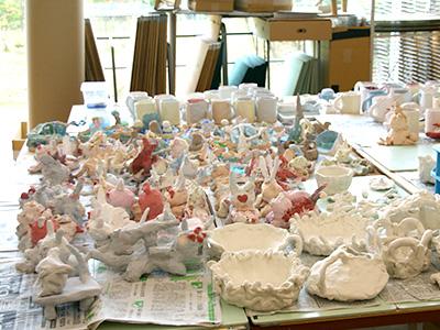 3年生による、制作中の「泉のある島」(写真上)。陶芸をする時期には、こうした制作途中の作品が図工室の一画を埋め尽くします。
