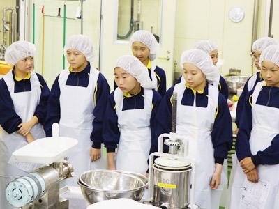 骨抜き作業を見つめ、不安と緊張が入り混じった表情をする生徒たち。