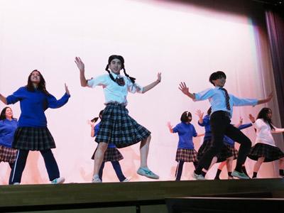 三つ編みのカツラを被り、スカート姿で踊る男子生徒(前方中央)。
