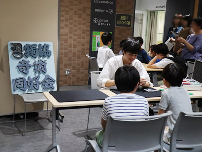 獨協中学校と高輪中学校の生徒がテーブルマジックを披露。子どもたちは夢中になって見入っていました。
