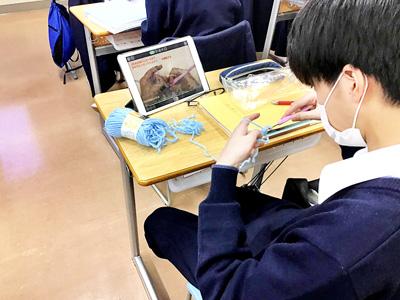 カギ針を使ってアクリルたわしを作る男子生徒