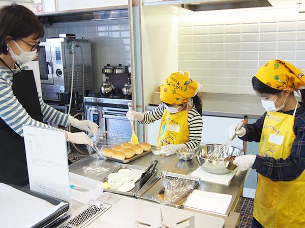 ロールパンに牛乳を塗っている妹の横で、お姉ちゃんはクッキー生地の準備
